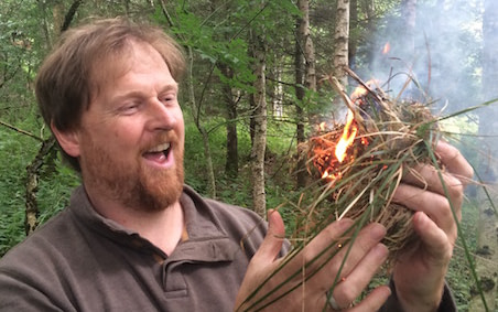 Malcolm holding a tinder nest and fire in his hands