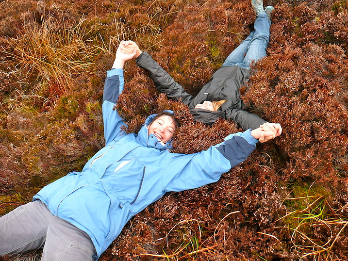 Two women holding hands lying down in heather